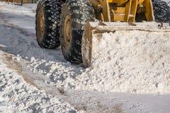 Máquina de la nieve de la retirada de la nieve en el camino en primavera imagenes de archivo