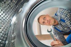 Máquina de lavar de Looking Inside The do reparador foto de stock