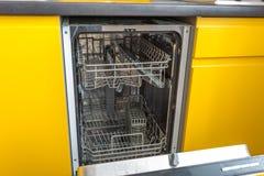 Máquina de lavar louça aberta na cozinha amarela fotos de stock royalty free