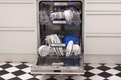 A máquina de lavar louça carrega em uma cozinha com os pratos limpos Imagens de Stock