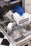 A máquina de lavar louça carrega em uma cozinha com os pratos limpos Imagem de Stock