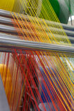 Máquina de matéria têxtil com as linhas vermelhas e amarelas das cores Foto de Stock Royalty Free