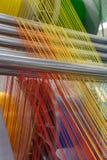 Máquina de materia textil con las cuerdas de rosca rojas y amarillas de los colores Foto de archivo libre de regalías