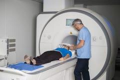 Máquina de mentira de la exploración del CT del paciente femenino del doctor Fixing Mask To Fotografía de archivo libre de regalías