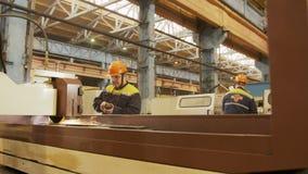 A máquina de moedura automatizada opera-se e os trabalhadores que verificam o processo video estoque