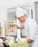 Máquina de Operating Spaghetti Pasta do cozinheiro chefe na cozinha Fotografia de Stock
