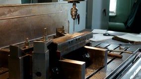 A máquina de perfuração fura uma abertura em um workpiece do metal, a fabricação de peças e os conjuntos, produção e filme