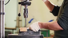 Máquina de perfuração industrial - o trabalhador faz furos no metal filme