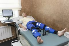 Máquina de Pressotherapy en hombre en centro médico del balneario Dispositivos cosméticos de la medicina fotos de archivo