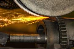 Máquina de pulir del primer, moliendo con las chispas una rueda de engranaje en la industria del automóvil imagen de archivo libre de regalías