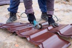 Máquina de pulir del uso del trabajador para cortar de la hoja de la techumbre del metal fotografía de archivo libre de regalías