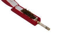 Máquina de rellenar del cigarrillo que rellena la cuenta de dólar diez Fotografía de archivo libre de regalías