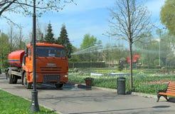 Máquina de riego en la madrugada en el parque público Moscú, Rusia Imagen de archivo