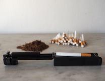 Máquina de rolamento do cigarro com cigarros vazios e cigarro no fundo Fotografia de Stock
