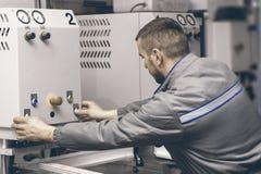 Máquina de soldadura de funcionamento do trabalhador na fábrica Janela plástica e imagens de stock royalty free