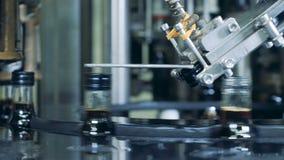 Máquina de trabajo que coloca los casquillos en las botellas, producción alcohólica almacen de metraje de vídeo