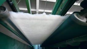 A máquina de trabalho rola o material não tecido em uma fábrica video estoque