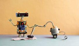 Máquina del aspirador del robot Alfombra robótica de la limpieza del juguete del Cyborg, fondo amarillo de la pared Fotos de archivo