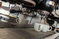 Máquina del café que sirve dos tazas blancas con descensos de las reflexiones, del vapor y del agua foto de archivo