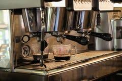 Máquina del café y dos tazas con la preparación de la escala Fotos de archivo libres de regalías