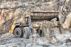 Máquina del cargador de la rueda que descarga rocas Imagen de archivo