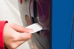 Máquina del estacionamiento de Person Hands Inserting Ticket Into Imágenes de archivo libres de regalías