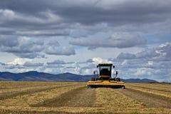 Máquina del heno en campo con las nubes dramáticas Foto de archivo