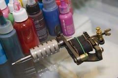 Máquina del tatuaje con las botellas de tinta Imagen de archivo libre de regalías