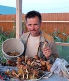 A máquina desbastadora alegre do cogumelo do homem recolheu muitos cogumelos comestíveis no sorriso da tabela feliz fotografia de stock
