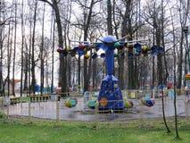 Máquina do balanço do ` s da criança no outono Um carro do brinquedo para crianças na jarda fotos de stock