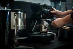 Máquina do café com mão no processamento Fotografia de Stock Royalty Free