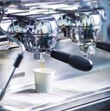 A máquina do café derrama o café em um vidro Processo de fatura do americano Beba no copo do Livro Branco sem etiqueta fotografia de stock