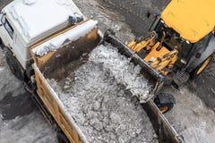 Máquina do carregador do trator que transfere arquivos pela rede a neve suja no caminhão basculante Rua de limpeza da cidade, rem imagens de stock