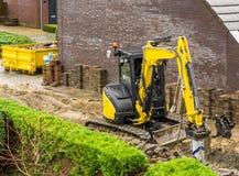 Máquina do escavador que trabalha em uma construção do jardim em uma vizinhança moderna imagens de stock
