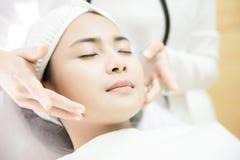 Máquina do laser Jovem mulher que recebe o tratamento do laser Cuidado de pele Jovem mulher que recebe o tratamento facial da bel foto de stock