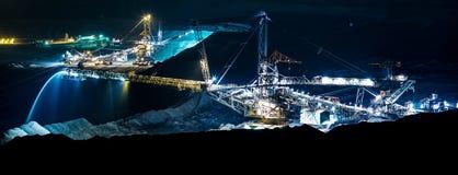 Máquina en una mina de carbón abierta en la noche Fotos de archivo libres de regalías