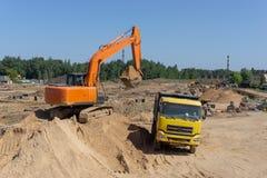 Máquina escavadora alaranjada e caminhão amarelo fotos de stock royalty free