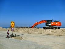 Máquina escavadora alaranjada na pilha da areia com sinais de estrada na construção Imagem de Stock