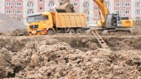 A máquina escavadora amarela carrega a argila usando sua cubeta grande video estoque
