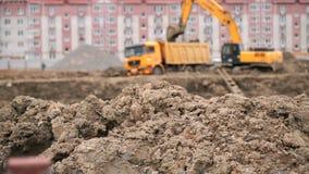 A máquina escavadora amarela carrega a argila usando sua cubeta grande filme