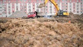 A máquina escavadora amarela carrega a argila usando sua cubeta grande vídeos de arquivo