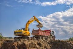 Máquina escavadora amarela e caminhão basculante vazio foto de stock royalty free