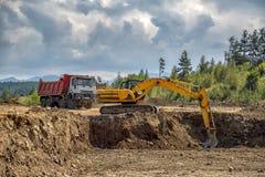 Máquina escavadora amarela e caminhão vazio imagens de stock