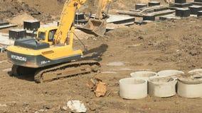 Máquina escavadora amarela em um canteiro de obras no verão vídeos de arquivo
