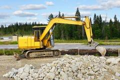 Máquina escavadora amarela na construção rodoviária Foto de Stock Royalty Free