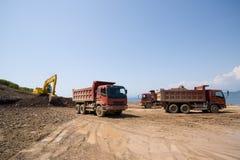 Máquina escavadora & caminhões de descarga imagens de stock royalty free