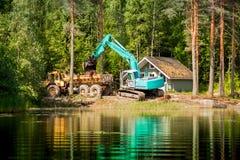 A máquina escavadora azul cancela a costa do lago foto de stock royalty free