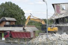 A máquina escavadora carrega o desperdício da construção no caminhão A cubeta da máquina escavadora derrama restos na parte trase imagem de stock