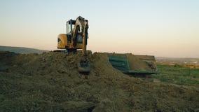 A máquina escavadora carrega um caminhão video estoque