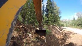 Máquina escavadora com a cubeta que escava uma trincheira vídeos de arquivo